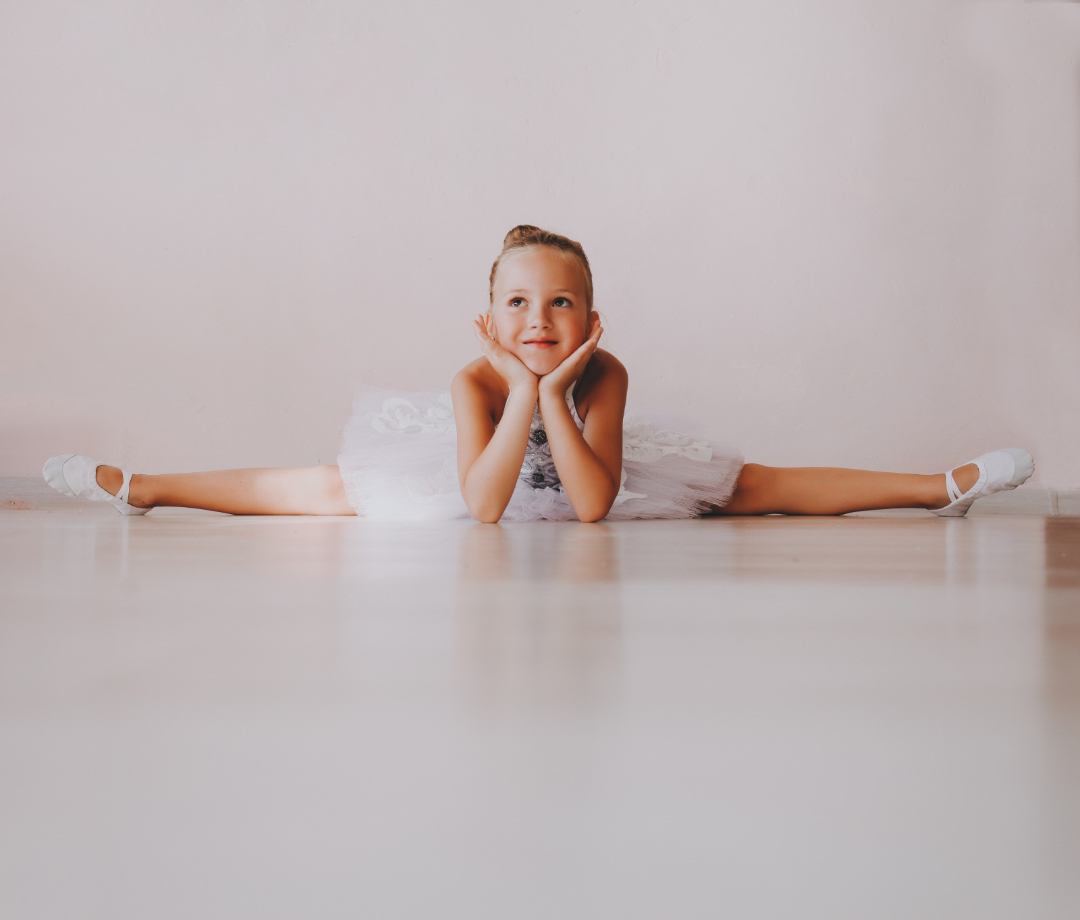 Young smiling dancer enjoying online dance class wearing white leotard
